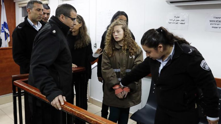 Sixteen-year-old Ahed Tamimi (C) arrives for a hearing in the military court at Ofer military prison in the West Bank village of Betunia on January 1, 2018.  Israeli authorities are seeking 12 charges against Ahed  after a video of her slapping and kicking two Israeli soldiers in the West Bank went viral, her lawyer said. / AFP PHOTO / Ahmad GHARABLI